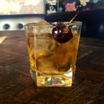 Our Godfather cocktail with whiskey, amaretto and cherry.